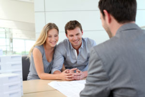 Couple in real-estate agency talking, part of the home page slide show.