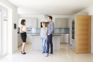 Realtor Showing Young Couple Around Property For Sale, standing in a kitchen part of the home page slide show